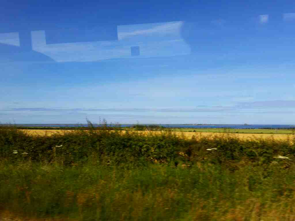View of Holy Island and Lindisfarne castle from the A1 on a X15 Newcastle to Berwick bus